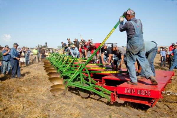 Jim Briden looks on his construction of assembling the two John Deere plows together during the first pass plowing. Brian Krog drops in the first bottom.